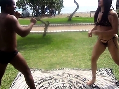 Dominant redhead in a hot bikini wrestles with a guy outside