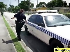 Two busty police officers in outdoor action with black dude