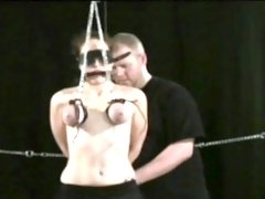 Pliant hottie stands and endures breast slavery porn
